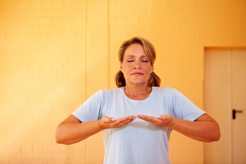 Relaxed woman doing breathing exercises in gym
