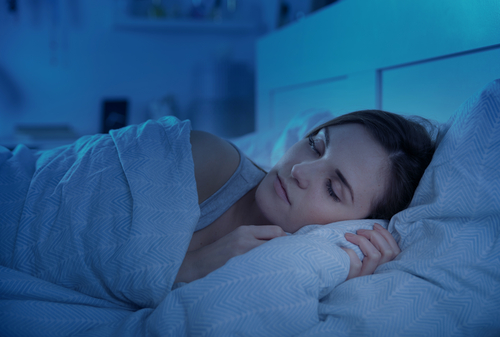 Woman peacefully sleeping in bed at night