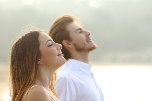 man and woman breathing deep fresh air together at sunset