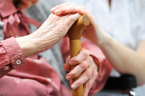 senior woman with caregiver hands