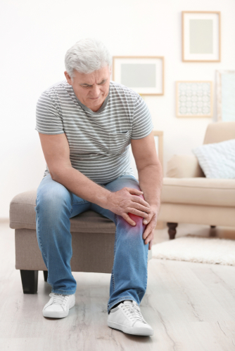 Senior man suffering from knee pain at home